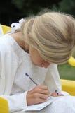 Flicka i den vita klänningen som skriver Fotografering för Bildbyråer