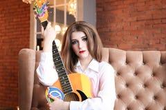 Flicka i den vita skjortan som poserar med en gitarr i hippiestil Arkivbild