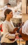 Flicka i den vita traditionella kl?nningen och b?rande fiol royaltyfri fotografi