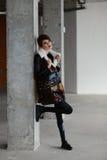Flicka i det bruna pälslaget som poserar på bakgrunden av väggen av röd tegelsten Fotografering för Bildbyråer