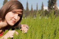 Flicka i det gröna gräset på en mjuk bakgrund av staden Arkivfoton