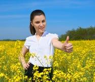 Flicka i det gula fingret för tumme för show för blommafält och leendet, bästa gest, härligt vårlandskap, ljus solig dag, rapsfrö Royaltyfri Bild