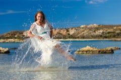Flicka i det plaskande vattnet för hav Arkivfoto