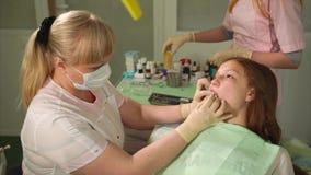 Flicka i det tand- kabineda sammanträdet i fåtölj Tandläkare som arbetar med hennes tänder lager videofilmer