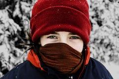Flicka i djup vinter med den förklädda framsidan Arkivfoton