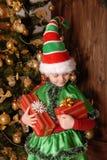 Flicka i dräkt av julälvan med en gåva Fotografering för Bildbyråer
