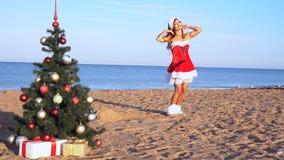 Flicka i dräkt på den nya semesterorten på stranden med gåvor 1 stock video