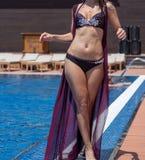 Flicka i en bikini av simbassängen för strandsemesterort Arkivfoto