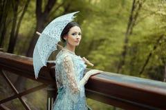 Flicka i en blå gammalmodig klänning Fotografering för Bildbyråer