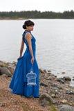 Flicka i en blå klänning med en tom fågelbur Arkivbild