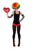 Flicka i en clowndräkt som rymmer en röd hjärta arkivbild