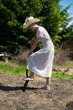Flicka i en cowboyhatt med skyffeln som gräver hålet Royaltyfria Foton