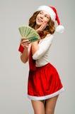 Flicka i en dräkt och en jultomtenhatt Håll pengar och att se upp excitedl Arkivbilder