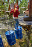 Flicka i en Forest Rope Park Challenge Royaltyfri Bild