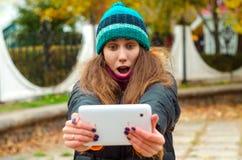 Flicka i en grön hatt som ser plattan med överraskning royaltyfri bild