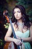 Flicka i en grön klänning med en violoncell Royaltyfri Fotografi