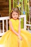 flicka i en gul klänning på en bänk fotografering för bildbyråer