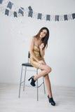 Flicka i en guld- klänning Royaltyfri Foto