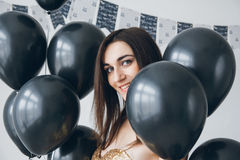 Flicka i en guld- klänning med svarta ballonger Royaltyfri Fotografi