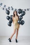 Flicka i en guld- klänning med svarta ballonger Arkivfoton
