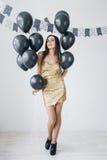 Flicka i en guld- klänning med svarta ballonger Royaltyfria Foton