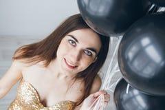 Flicka i en guld- klänning med svarta ballonger Royaltyfria Bilder
