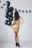 Flicka i en guld- klänning med svarta ballonger Royaltyfri Foto