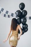 Flicka i en guld- klänning med svarta ballonger Arkivbild