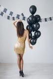 Flicka i en guld- klänning med svarta ballonger Arkivfoto