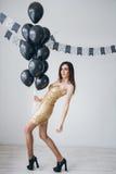 Flicka i en guld- klänning med svarta ballonger Arkivbilder