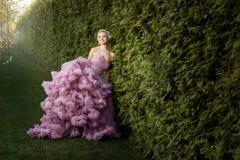 Flicka i en härlig rosa färgklänning Arkivfoton