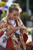 Flicka i en halsduk och en gammal rysk dräkt av det 19th århundradet Royaltyfri Bild