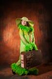 Flicka i en hatt med en gammal resväska royaltyfria bilder