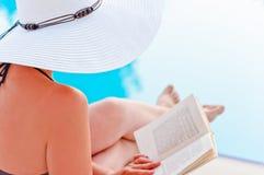 Flicka i en hatt som läser en bok nära pölen som sitter i en vardagsrumstol Royaltyfri Fotografi