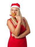 Flicka i en hattjultomtenhjälpreda som äter godisrottingen Fotografering för Bildbyråer
