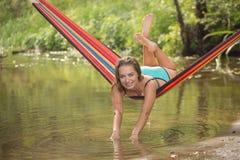 Flicka i en hängmatta över vattnet Royaltyfria Bilder