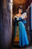 Flicka i en inre i en forntida klänning Arkivbild