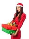 Flicka i en jultomten gåvor för jul för hjälpredahatt hållande Royaltyfria Bilder