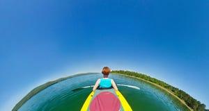 Flicka i en kanot som svävar ner floden Fisköga royaltyfri fotografi