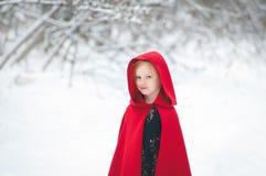 Flicka i en kappa med en huv royaltyfri foto