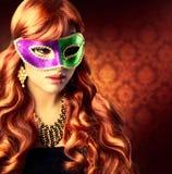 Flicka i en karnevalmaskering Arkivfoto