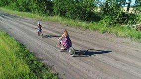 Flicka i en klänning med ett barn som rider en cykel längs veteåkrar Skjuta med surret Härligt landskap från a stock video