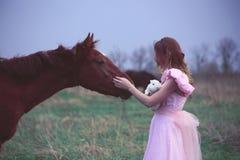 Flicka i en klänning nära en häst Arkivfoton