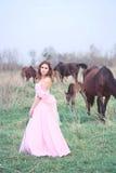 Flicka i en klänning nära en häst Royaltyfri Bild