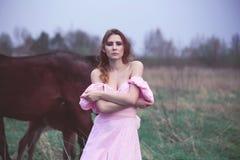 Flicka i en klänning nära en häst Royaltyfria Foton