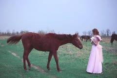 Flicka i en klänning nära en häst Arkivbilder
