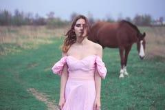 Flicka i en klänning nära en häst Royaltyfria Bilder