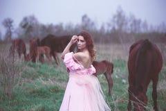 Flicka i en klänning nära en häst Royaltyfri Foto