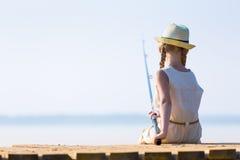 Flicka i en klänning och en hatt med en metspö Arkivbild