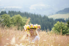 Flicka i en krans på en äng Royaltyfria Bilder